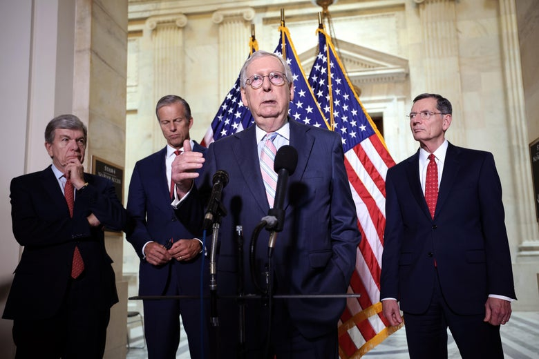 Mitch McConnell speaks at a mic with three other Republicans behind him