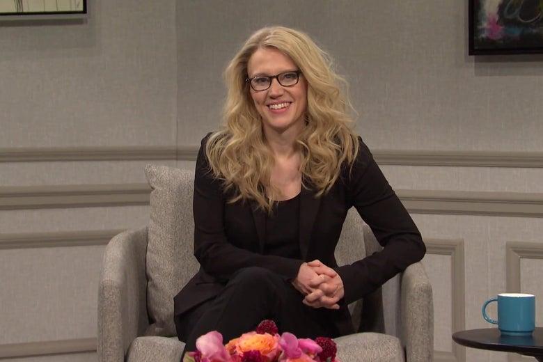 Kate McKinnon in a dark suit, sitting on a beige chair on a talk show set.
