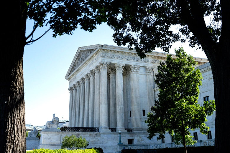 The Supreme Court is seen through some trees.