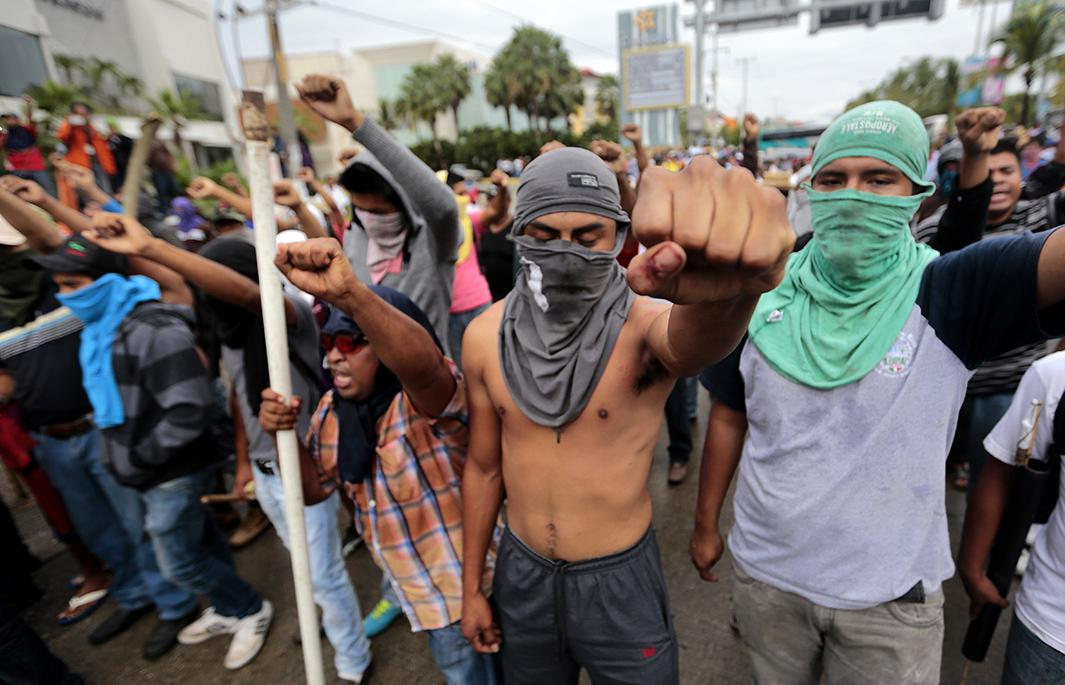 Students, farmworkers and other demonstrators confront the riot police during a protest near Acapulco in Guerrero state.
