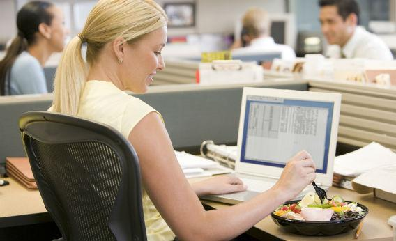 Woman eating at her desk.