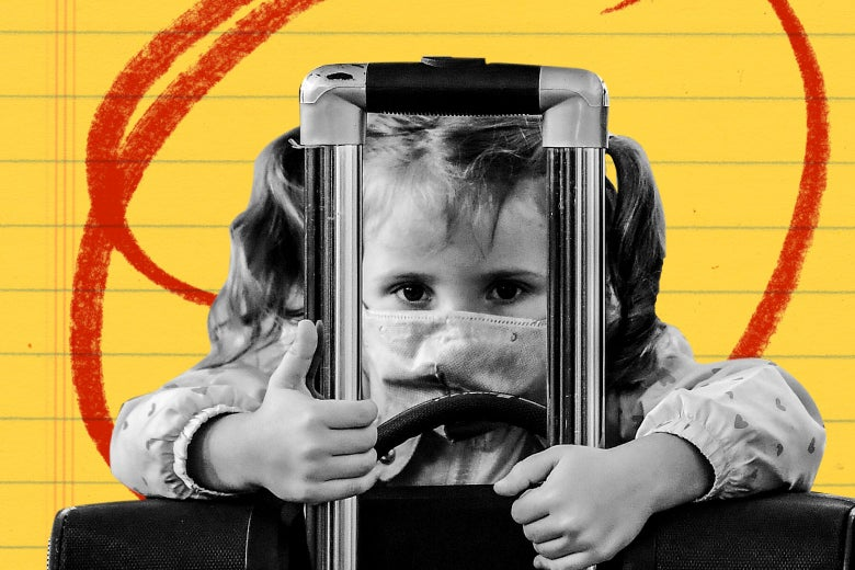 A little girl in pigtails wearing a surgical mask, with her arms wrapped around a luggage.