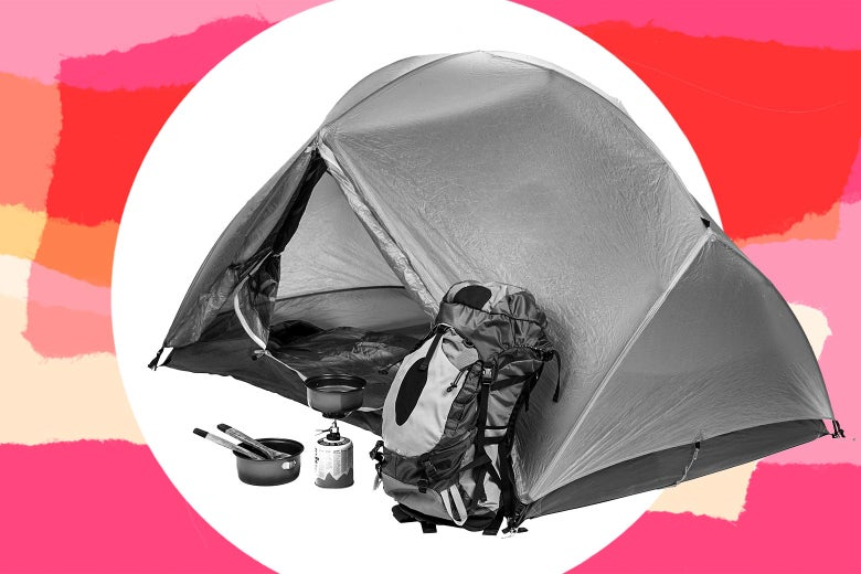 A tent with backpack and cooking gear outside it.
