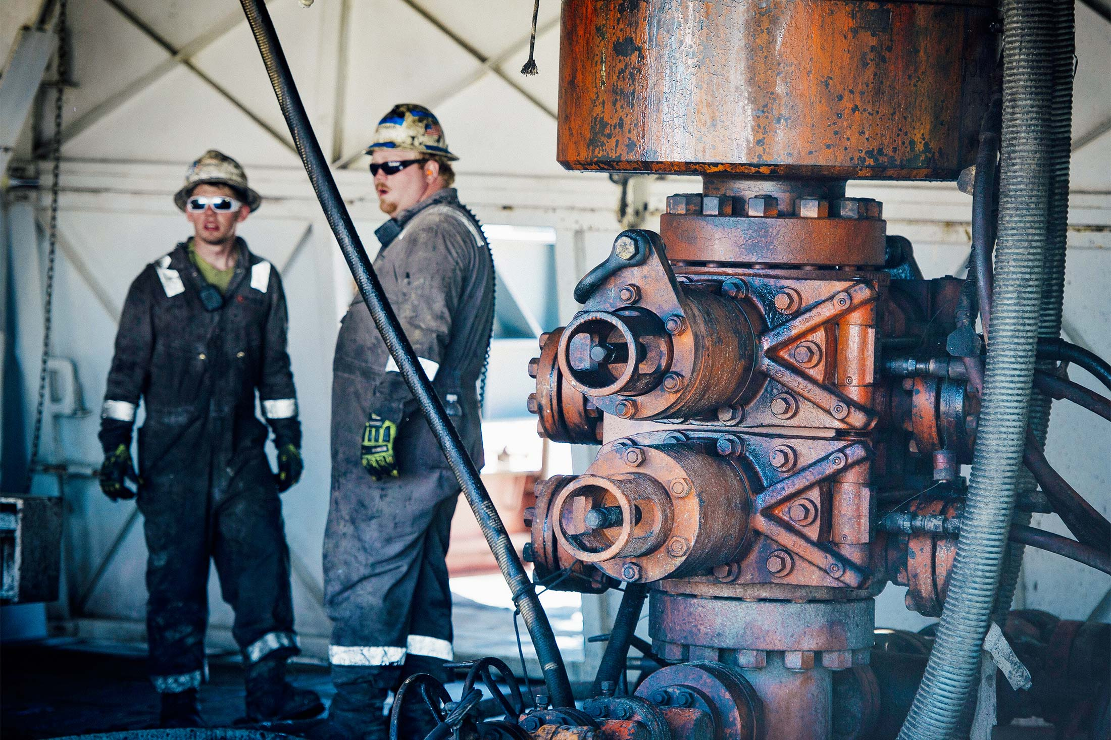 Workers chat beside a Consol Energy drilling rig.