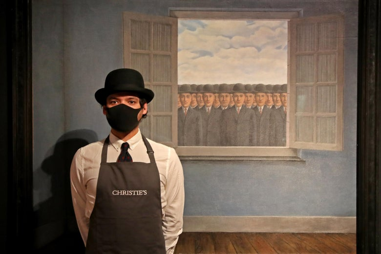 """An art worker wearing a bowler hat and a Christie's apron stands next to René Magritte's """"Le mois des vendanges"""" painting, which features an infinite number of men wearing bowler hats peering in an open window."""