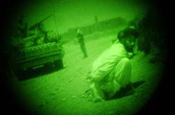 U.S. Special Forces tactical vehicle watches over a detainee during a night mission in 2004. Click to expand image.