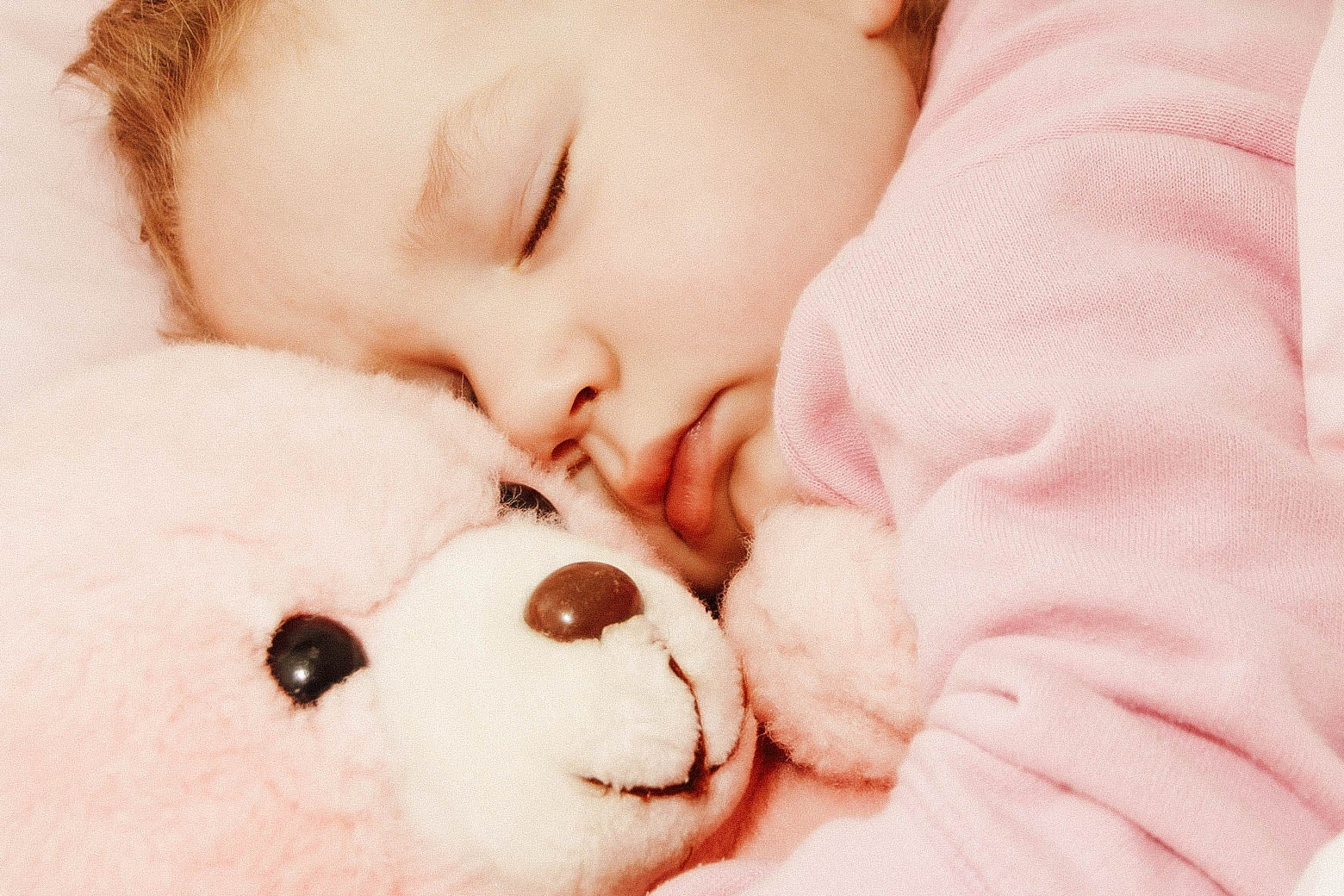A child in bed with a teddy bear.