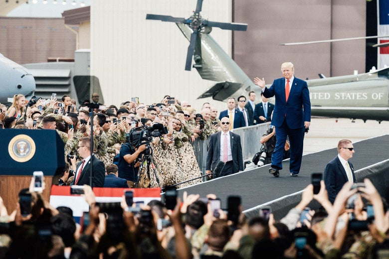 President Donald Trump waves to a crowd of troops and families.