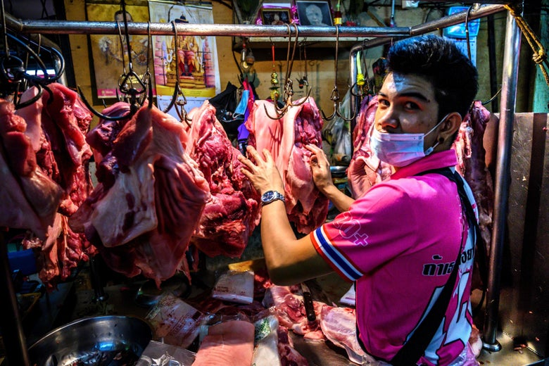 A masked man stands in front of meat on hooks.