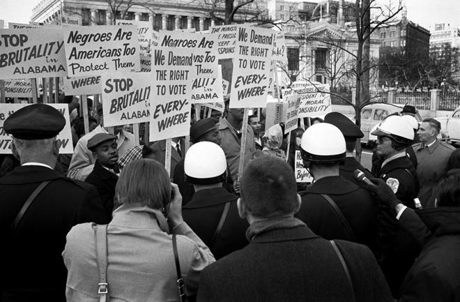 """Demonstrators outside the White House in Washington, D.C., hold signs saying """"We demand the right to vote, everywhere"""" and protesting police brutality against civil rights demonstrators in Selma, Alabama"""