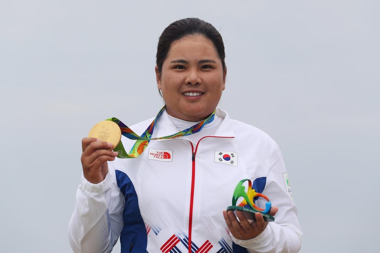 Gold medalist Inbee Park poses with her medal and the Rio Olympics logo statue.