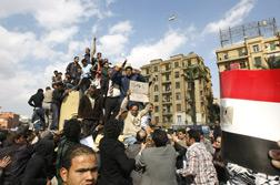An army helicopter flies overhead as Egyptians protest in Tahrir Square, in the capital Cairo, on Jan. 30, 2011, on the sixth day of mass demonstrations against Mubarak's regime amid increasing lawlessness, a rising death toll and a spate of jail breaks