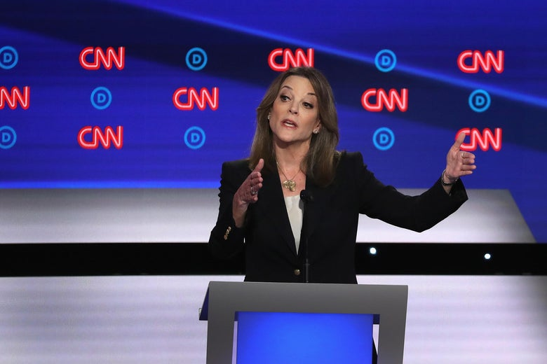 Marianne Williamson, in a dark suit, stands against a debate backdrop with the CNN logo repeating on it and makes a gesture with her hands as if measuring something in the air.