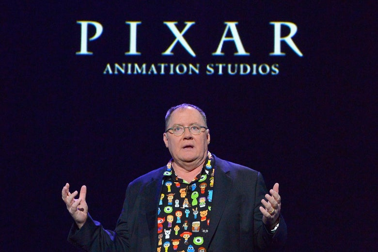 John Lasseter speaks onstage, wearing a shirt with cartoon characters underneath a blazer. He stands beneath the words Pixar Animation Studios projected onto a black wall.