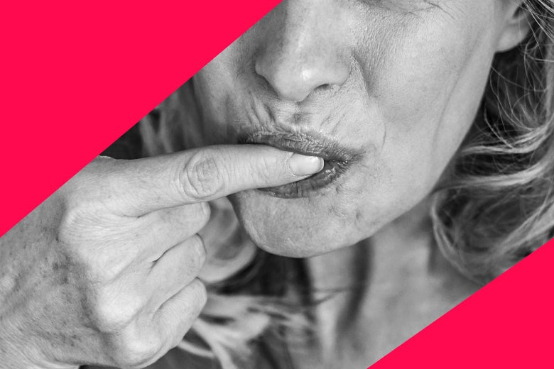 A woman sucking on her index finger.
