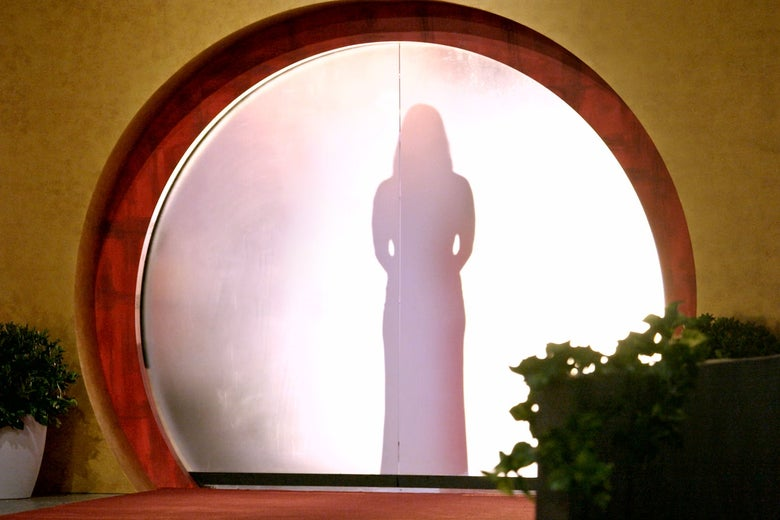 A female figure stands silhouetted in a smoky doorway.