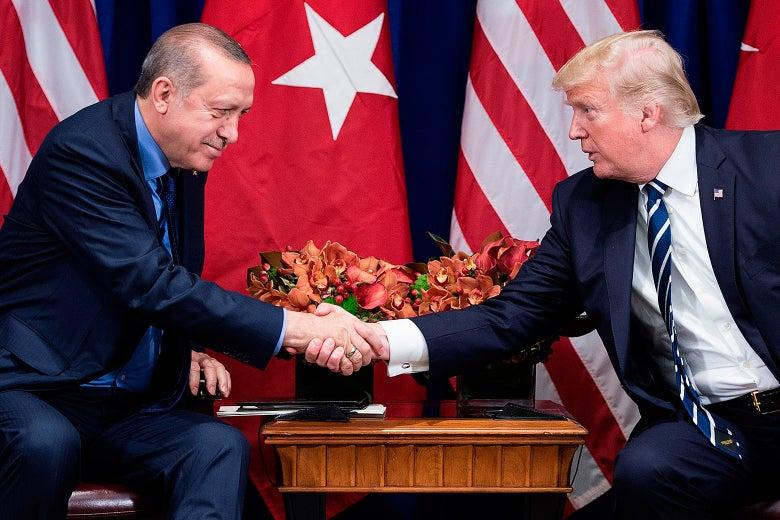 Recep Tayyip Erdogan and Donald Trump, seated, shake hands.