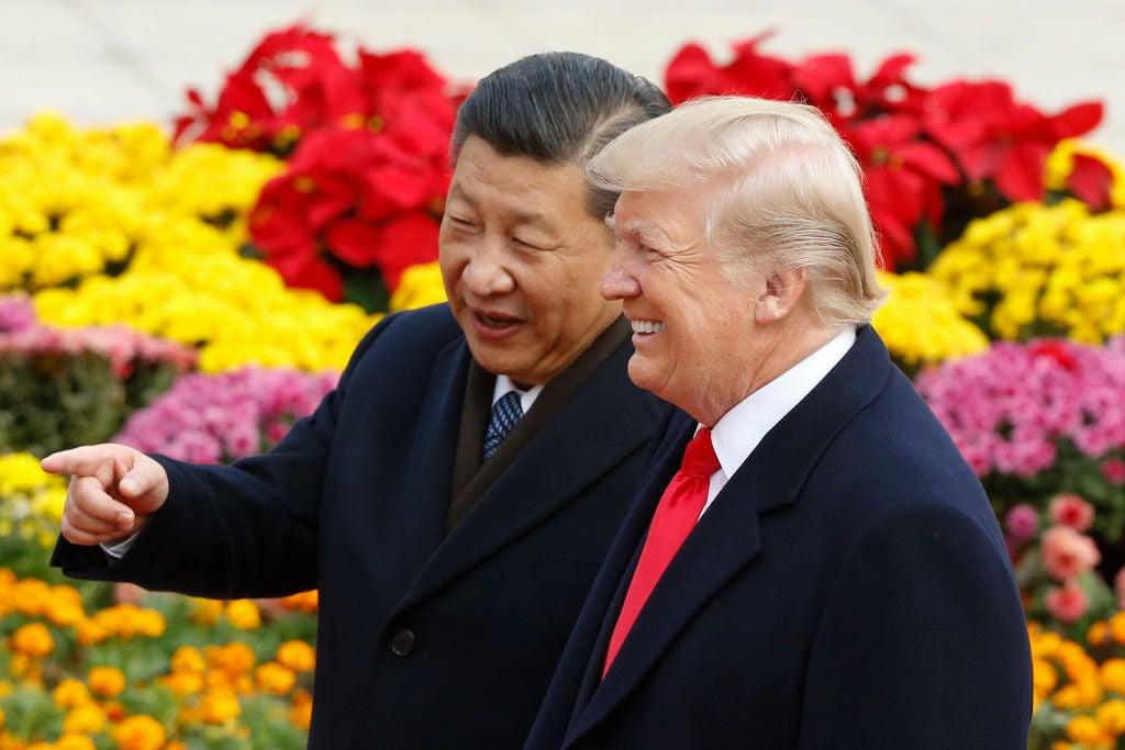 Xi and Trump stand in front of colorful flowers as Xi points and Trump smiles.
