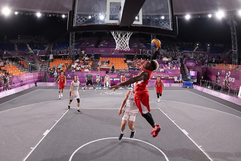 A player in a red jersey dunks over a player in a white jersey.