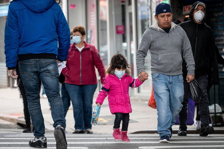 A girl and her father, wearing masks, walk across a crosswalk with other people.