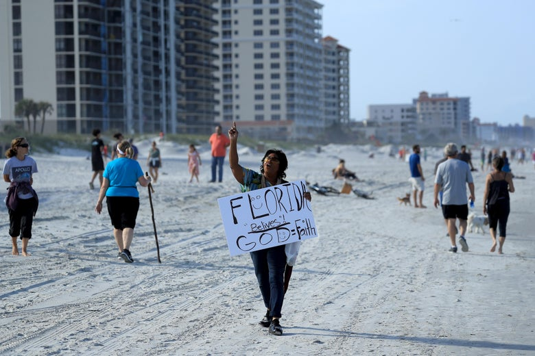 """People walking on the beach. One person carries a sign that says """"Florida belives! God = Faith."""""""