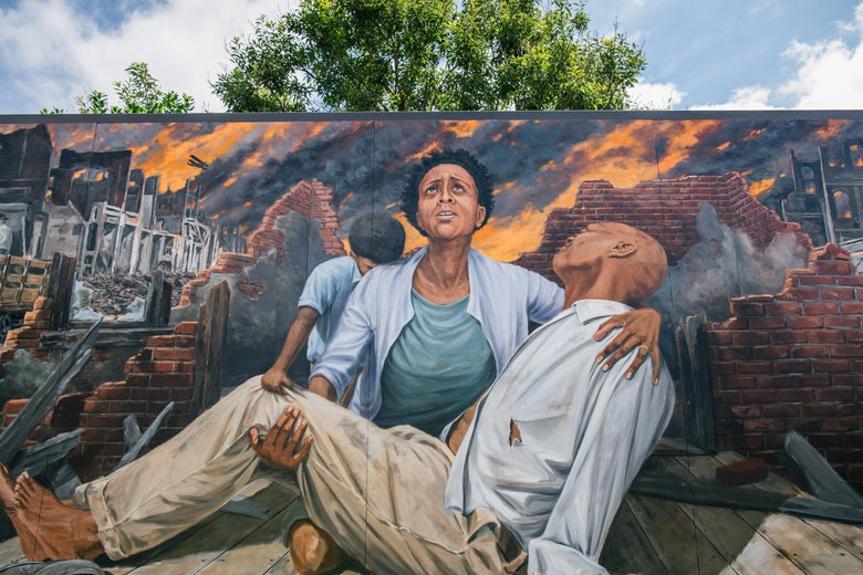 TULSA, OKLAHOMA - MAY 28 A mural depicting a woman and child holding a man during the Tulsa massacre.