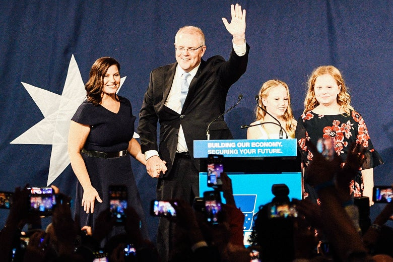 Scott Morrison waves to the crowd as he holds his wife's hand.