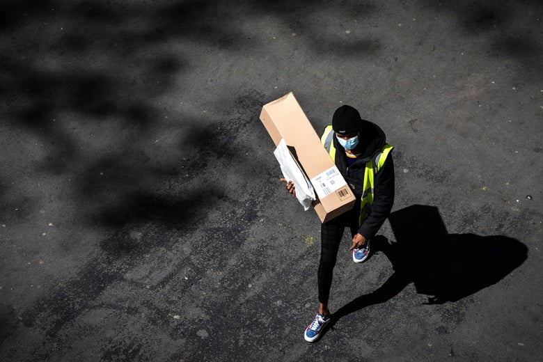 An aerial view of a person walking alone on a street. They're wearing black clothes, blue shoes, and a surgical mask, and they're carrying a box and a small parcel.