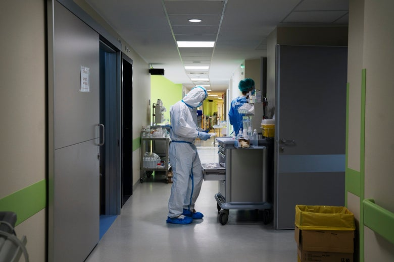 Medical workers in PPE in a hospital hallway.