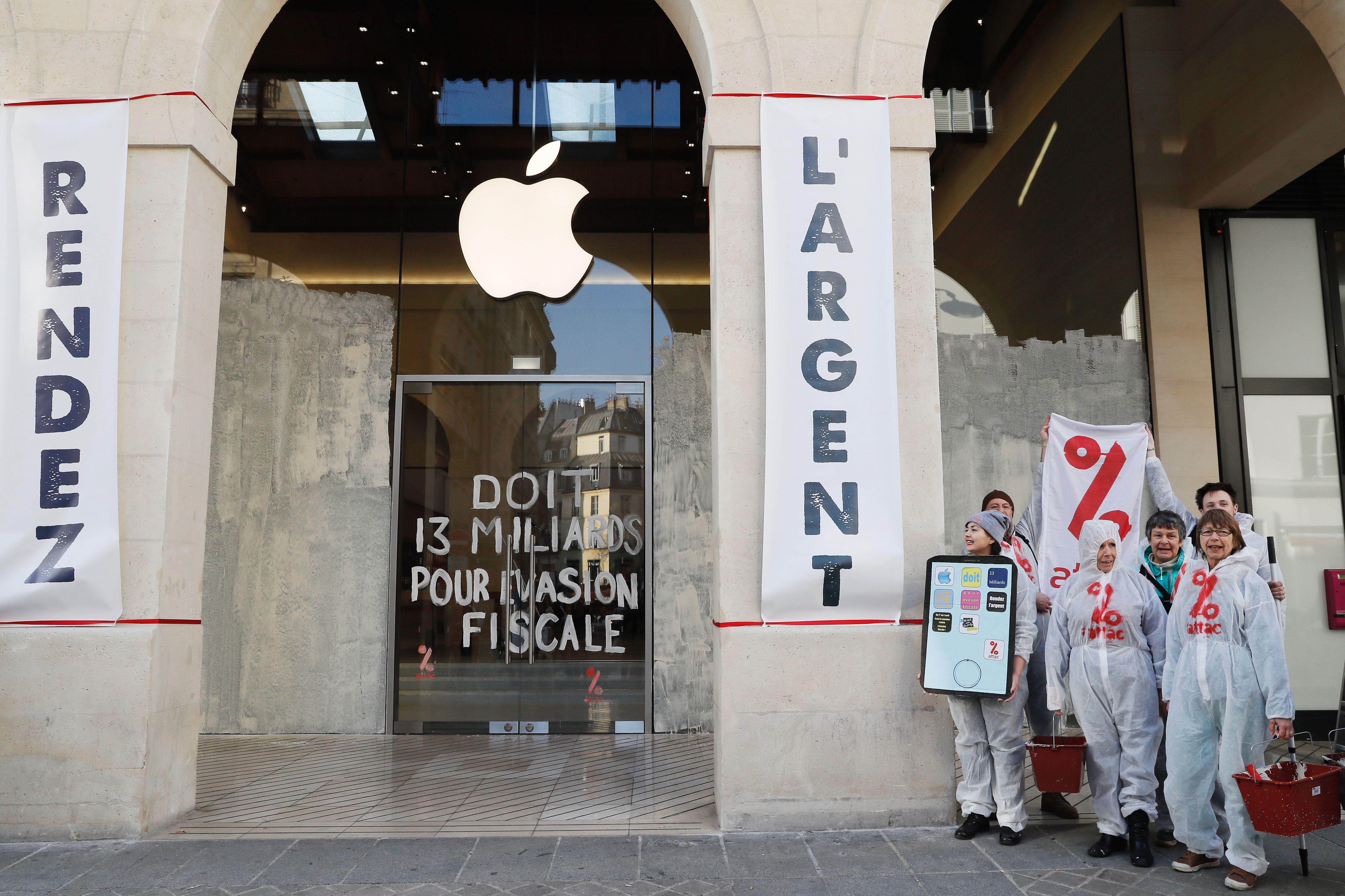 Activists from the Association for the Taxation of financial Transactions and Citizen's Action (ATTAC) pose with placards and an inscription which translate as 'Give the money back' and  '(Apple) owes 13 billion (euros) due to tax evasion' in front of an Apple store in Paris during a demonstration to denounce tax avoidance on March 13, 2017.