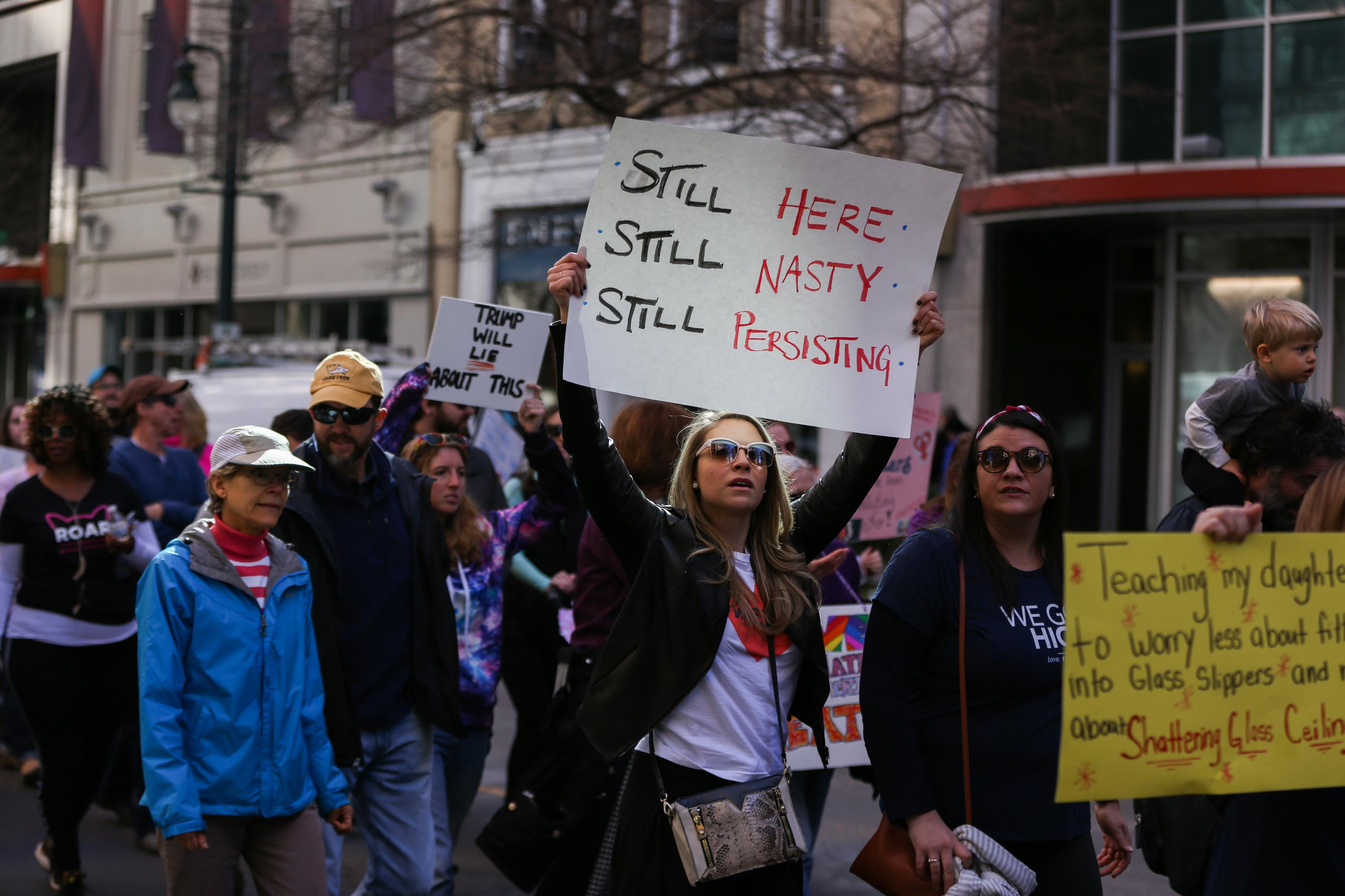 A woman holds up a sign at First Ward Park during the Remarchable Women rally in Charlotte, North Carolina on January 20, 2018, marking the one-year anniversary of the Women's March. / AFP PHOTO / Logan Cyrus        (Photo credit should read LOGAN CYRUS/AFP/Getty Images)