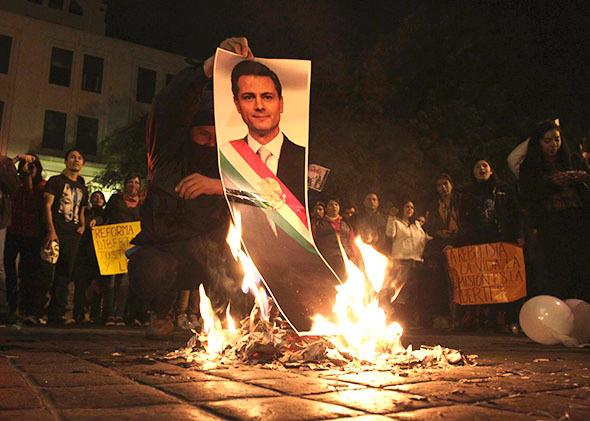 A demonstrator burns a photograph of Mexico's President Enrique Pena Nieto during a protest in support of the 43 missing Ayotzinapa students, in Monterrey November 20, 2014.