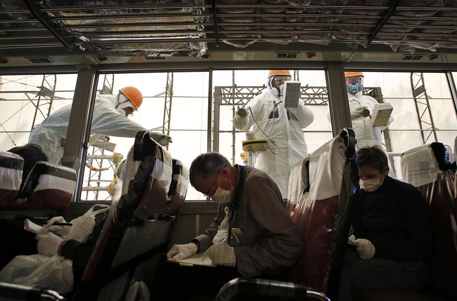 Workers carry out radiation screening on a bus for a media tour at Tokyo Electric Power Co. (TEPCO)'s tsunami-crippled Fukushima Dai-ichi nuclear power plant.