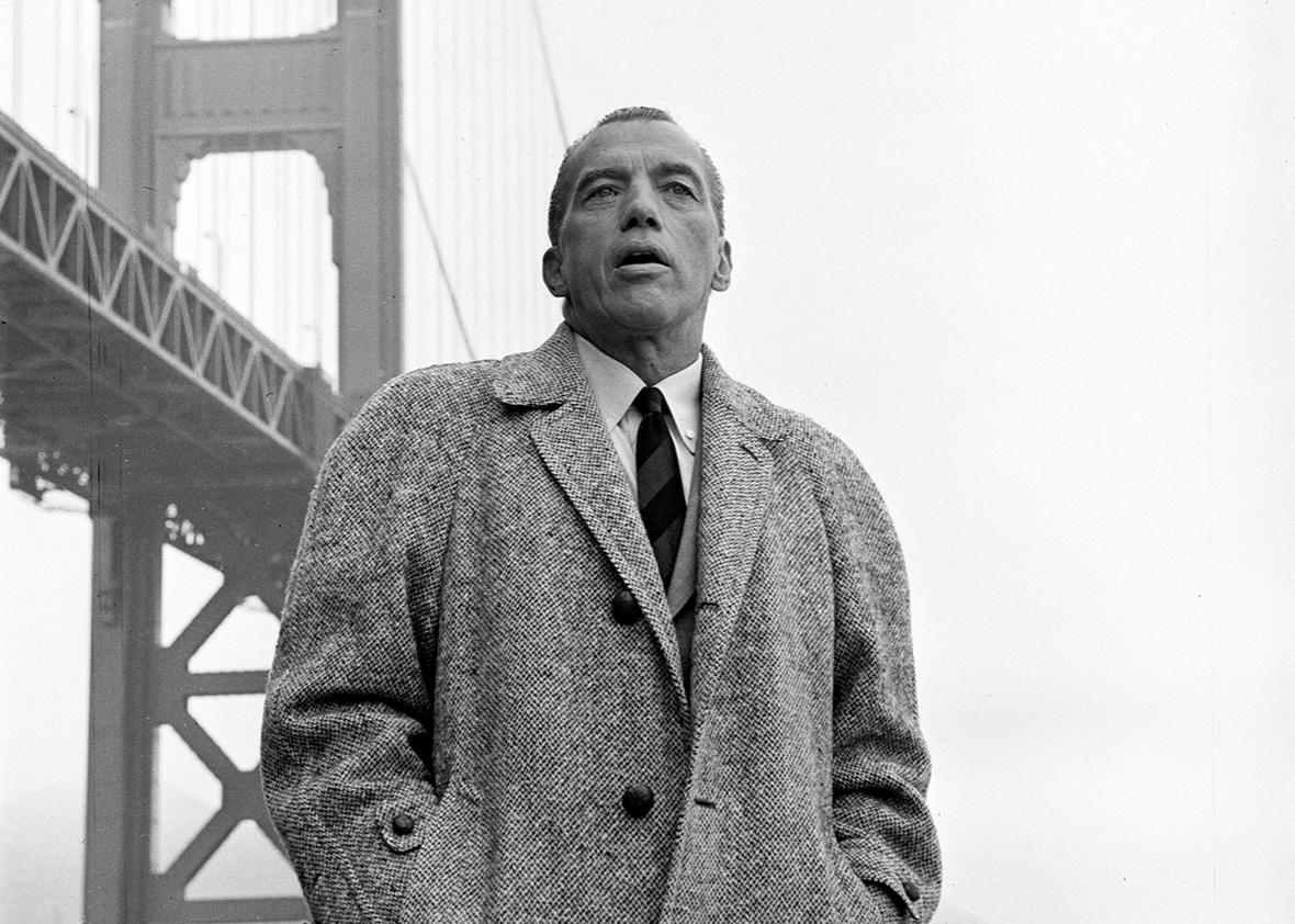 American television personality Ed Sullivan, dressed in an overcoat, stands in front of the Golden Gate Bridge during the filming of an episode of his tv show, San Francisco, California, September 17, 1960.