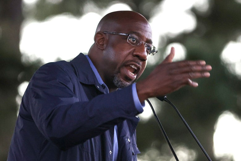 Raphael Warnock gestures while speaking into a microphone.