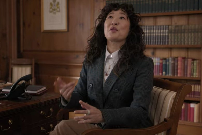 Dr. Kim sits in a chair in front of a bookshelf.