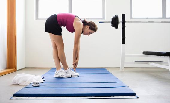 Young woman doing stretching exercise on mat in gym.