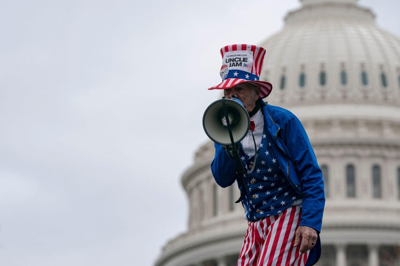 A man in an Uncle Sam costume speaks into a megaphone outside the U.S. Capitol.