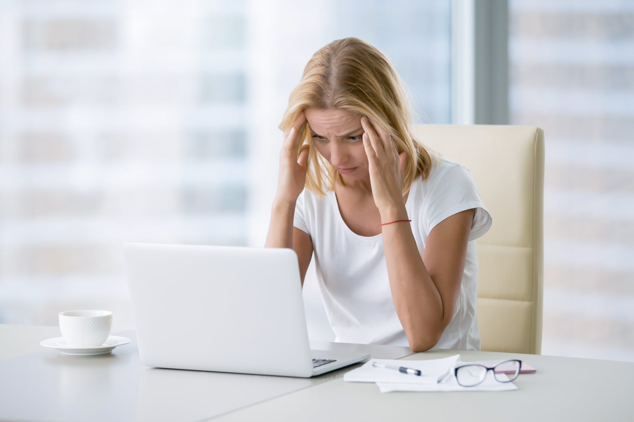 A woman in pain looking at a computer screen.