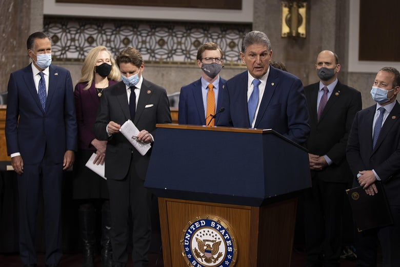Joe Manchin speaks at a podium, surrounded by colleagues in masks.