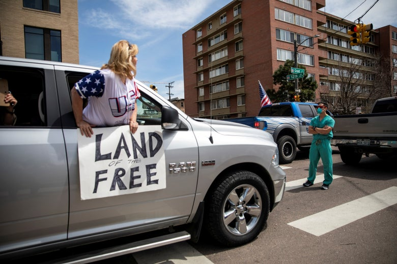 "A woman pokes her body out of the passenger seat of a car, carrying a sign saying ""Land of the Free."" In front of the car, a medical worker in a mask stands with arms crossed."