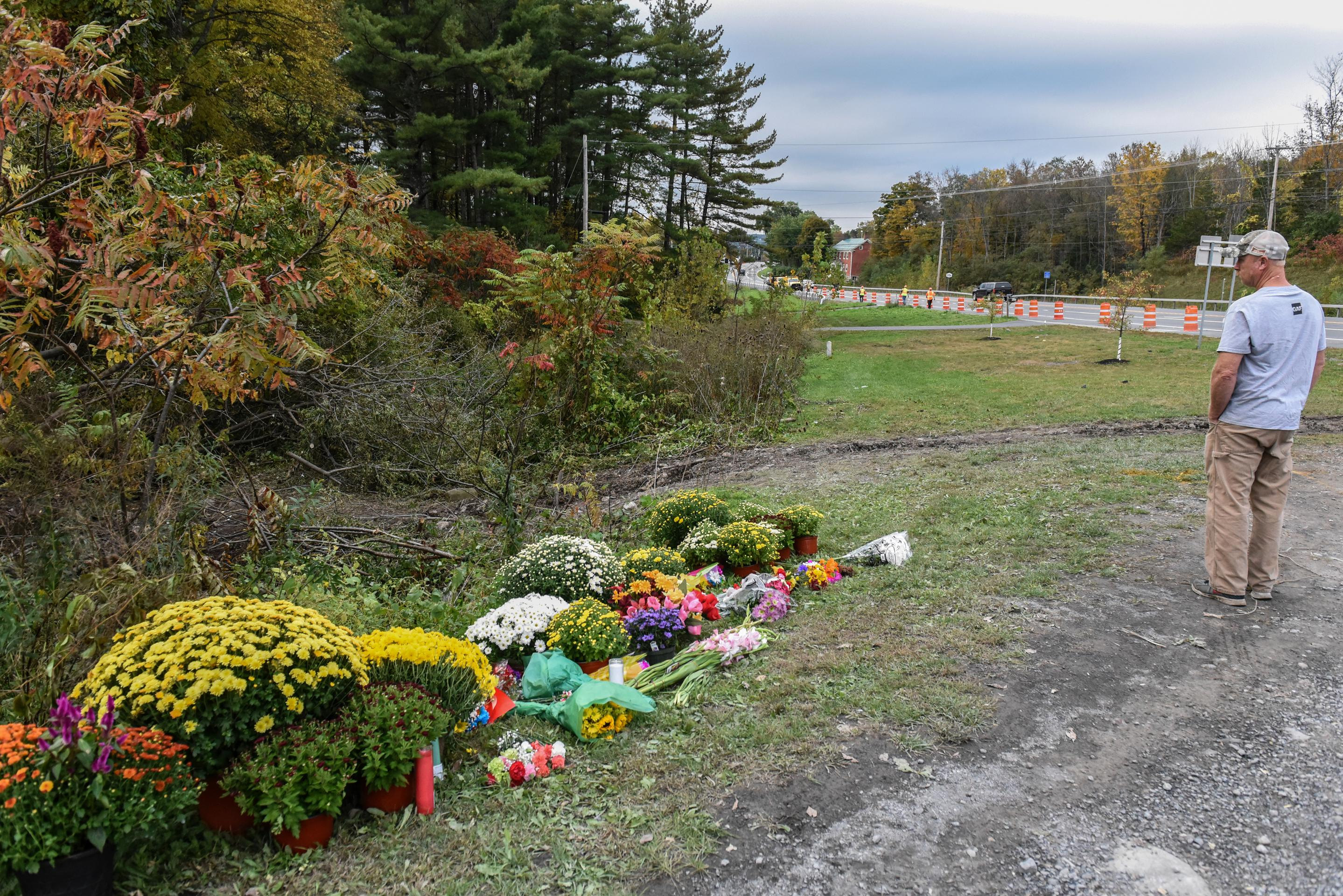 A man looking from the roadside onto a makeshift memorial of flowers.