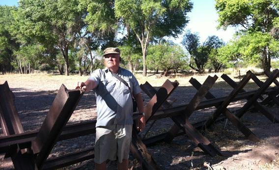 "Glenn Spencer stands near a five foot ""Normandy-style"" fence near his property, on the US-Mexico border."