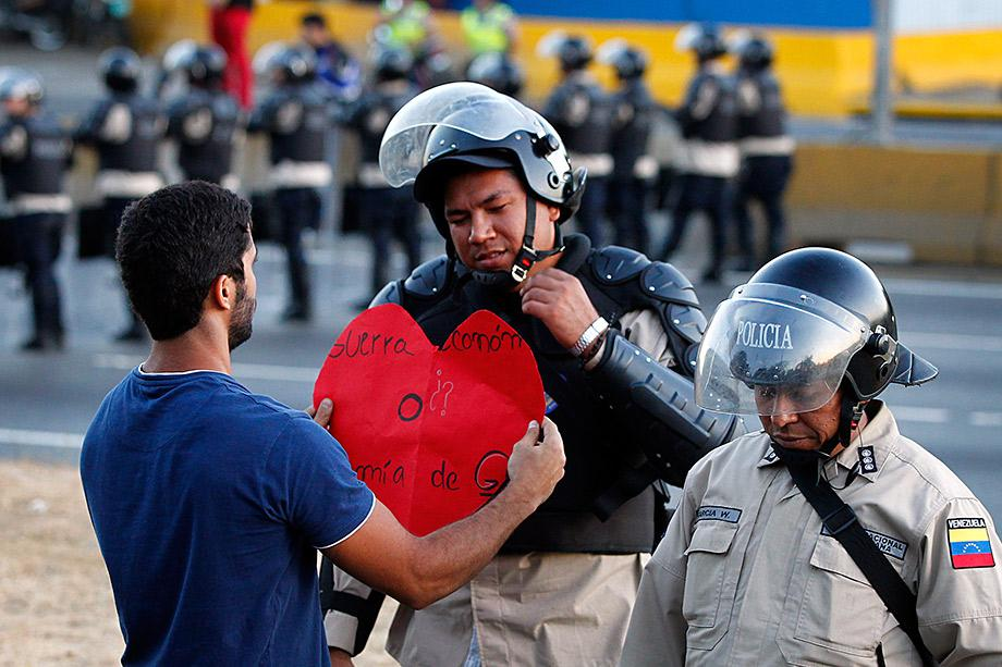 An opposition demonstrator gives a heart-shaped cutting to a police officer as demonstrators block the city's main highway during a protest against Nicolas Maduro's government in Caracas.