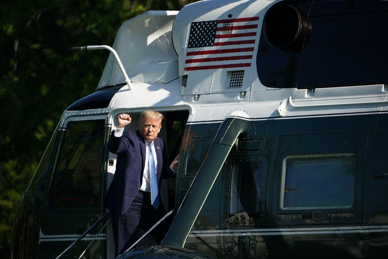 President Trump gestures with a fist as he boards Marine One helicopter.