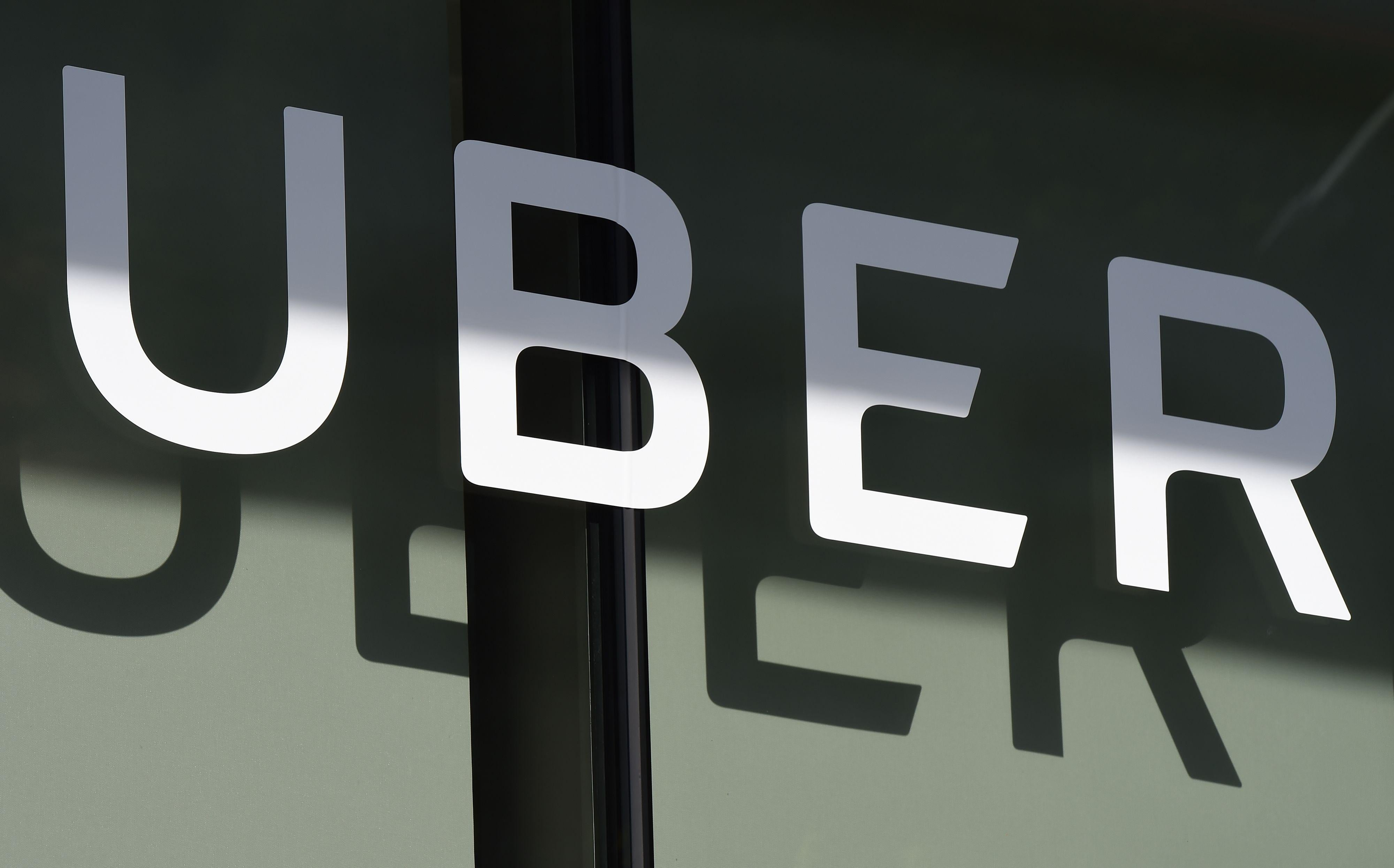 The Uber logo is seen at the second annual Uber Elevate Summit, on May 8, 2018 at the Skirball Center in Los Angeles, California. - Uber introduced it's electric powered 'flying taxi' vertical take-off and landing concept aircraft at the event, which showcases prototypes for UberAir's fleet of airborne taxis. (Photo by Robyn Beck / AFP)        (Photo credit should read ROBYN BECK/AFP/Getty Images)