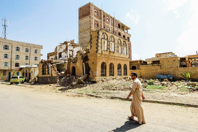 A man walks down a street in front of a destroyed building.