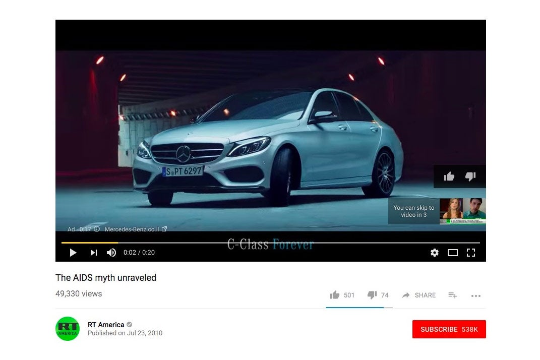 YouTube screenshot showing Mercedes-Benz commercial playing before an AIDS conspiracy video from RT America.