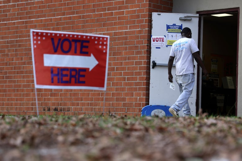 "A man walks through the open door of a brick building that has a ""Vote Here"" sign out front"