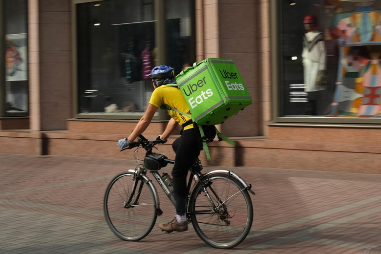 A man wearing a yellow shirt rides a bike past storefronts. On his back is a green Uber Eats container.